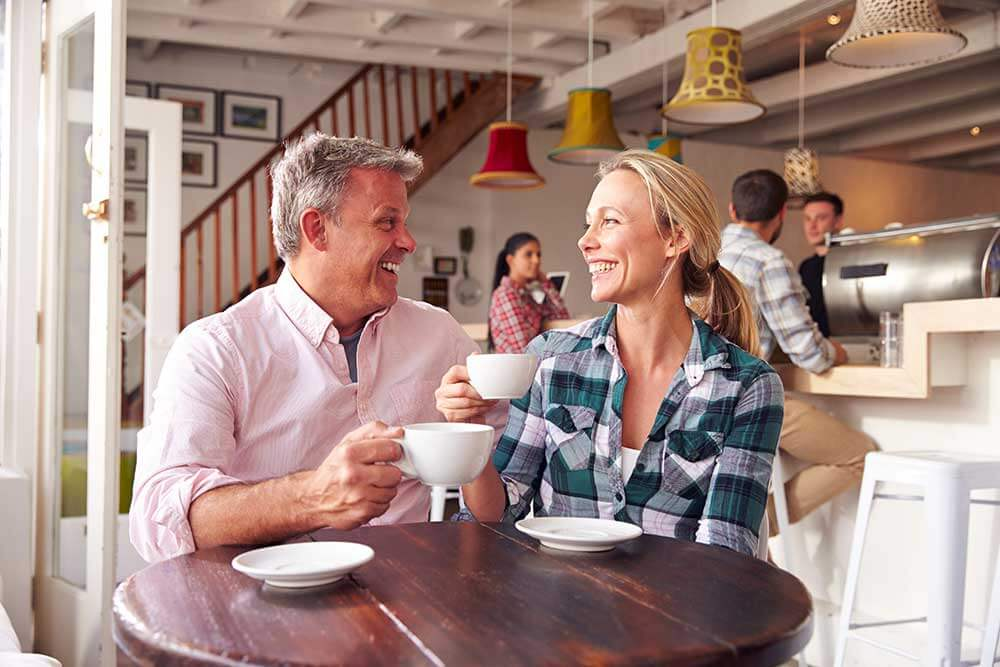 A man and woman are on a date and enjoying their smiles. The woman has porcelain veneers.