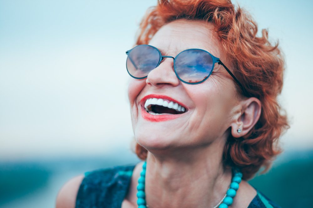 An older woman with red hair and sunglasses smiles, showing off her porcelain veneers.
